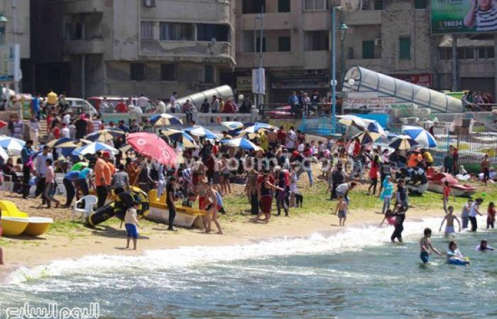"""بالصور.. شواطئ الإسكندرية تتمسك بـ""""شم النسيم"""" وتتحدى اضطرابات الطقس"""